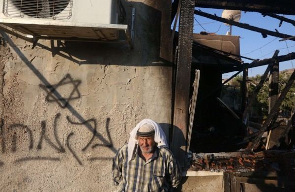 """Image: A Palestinian man stands next to a graffiti reading in Hebrew """"Revenge"""""""