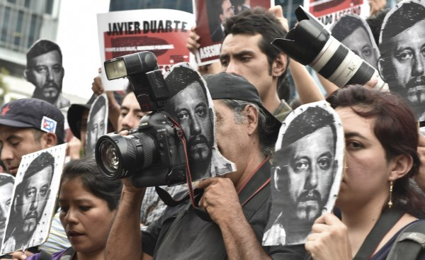 Image: Mexican photojournalists hold pictures of Ruben Espinoza