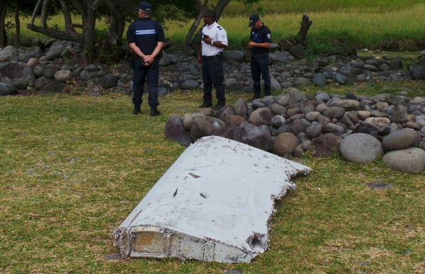 Image: Officials stand near plane debris which was found on Reunion Island