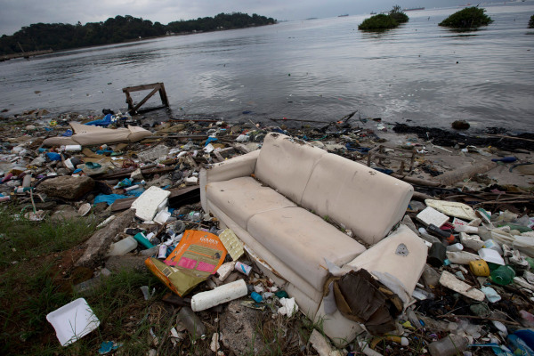 Image: A discarded sofa litters the shore of Guanabara Bay in Rio