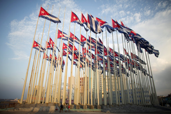 Image: Tourists take pictures of Cubans flags in front of U.S embassy in Havana