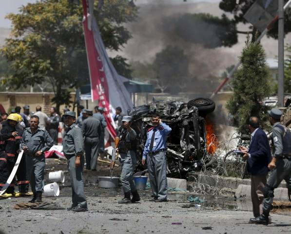 Image: Police stand at the site of a car bomb blast at the entrance gate to the Kabul airport