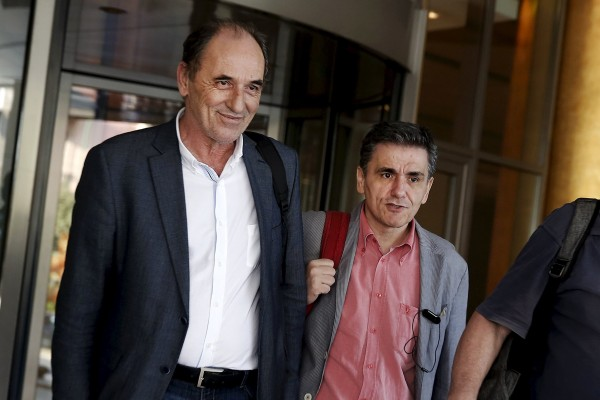 Image: Greek Economy Minister Stathakis and Finance Minister Tsakalotos leave a hotel following an overnight meeting in Athens