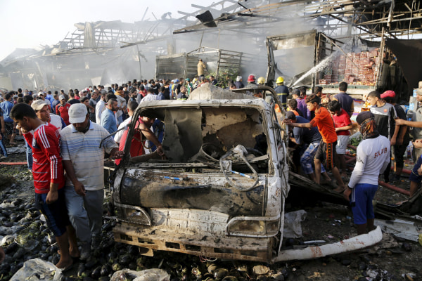 Image: Residents gather at the site of a truck bomb attack at a crowded market in Baghdad