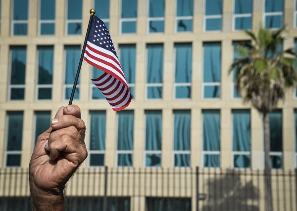 Image: A Cuban holds a little US flag in front of the US Embassy in Havana