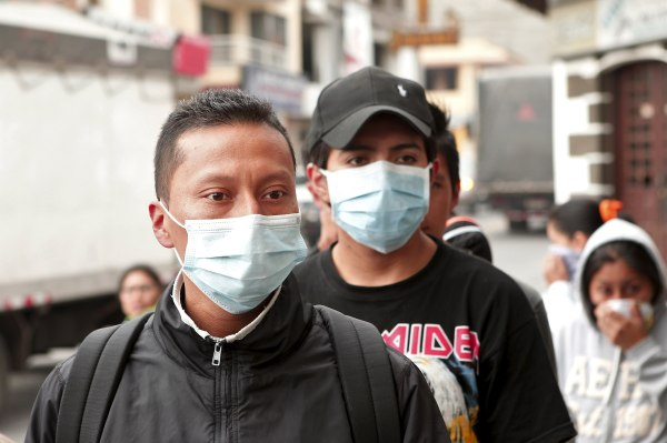Image: People wear surgical masks to protect themselves from volcanic ash in Machachi