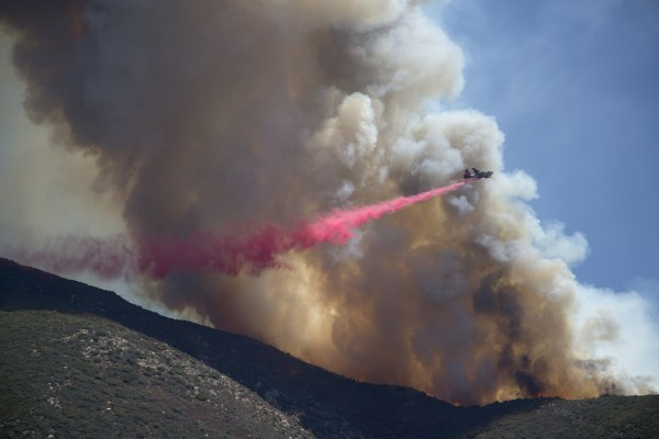 Image: Aircraft drops fire retardant at the Cabin Fire in the Angeles National Forest on Saturday