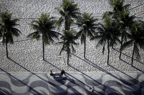 Image: People sit on a bench on the sidewalk at Copacabana Beach in Rio de Janeiro, Brazil