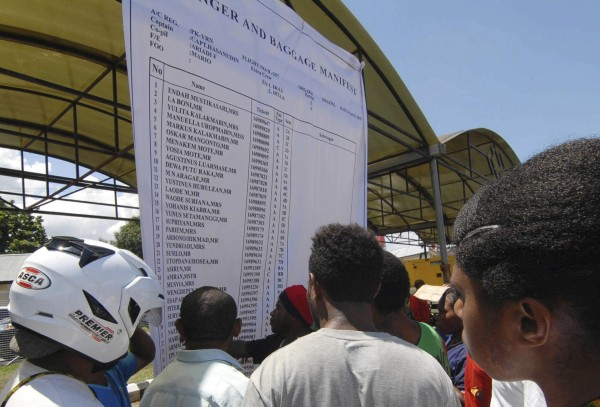 Image: People look at a passenger and baggage manifest of the crashed Trigana flight