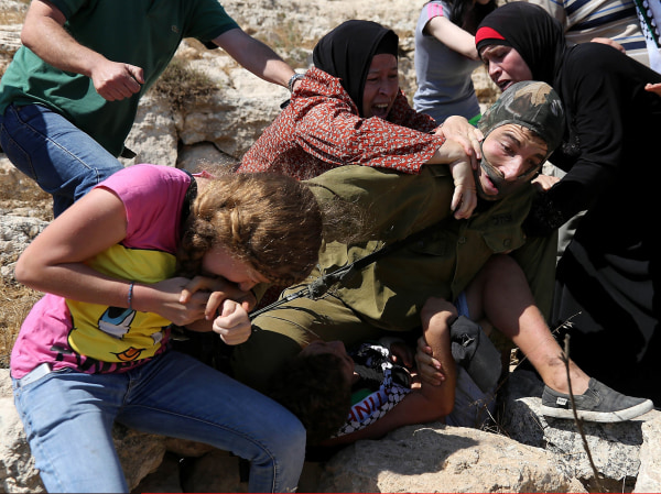 Image: Ahed Tamimi bites a masked Israeli soldier in the midst of a melee