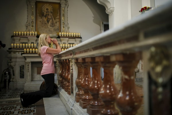 Image: A woman prays while people attend the last mass at Church of Our Lady of Peace in New York
