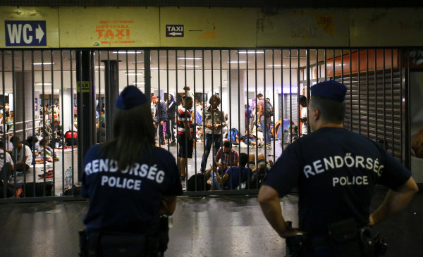 Image: Hungarian police guard refugees at a makeshift camp in an underground station near the Keleti train station in Budapest
