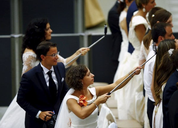 """Image: Newly married couples use a """"selfie stick"""" during Pope Francis' Wednesday general audience in Paul VI hall at the Vatican"""