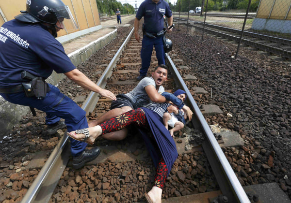 Image: Hungarian policemen apprehend a migrant family