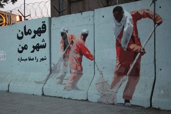 Image: A mural designed by Afghan artist Kabir Mokamel appears on a Kabul blast wall, depicting the city's street sweepers.