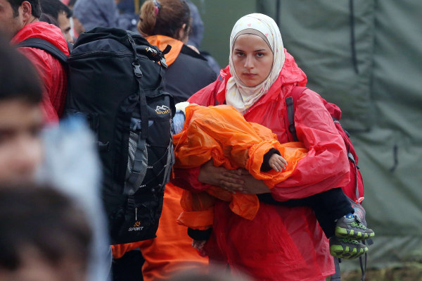 Image: A migrant woman carrying her child arrives