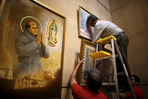 Image: Ramiro Montes hangs paintings in a new chapel in honor of Friar Junipero Serra, who will be canonized next week by Pope Francis, at the Cathedral of Our Lady of the Angels in Los Angeles