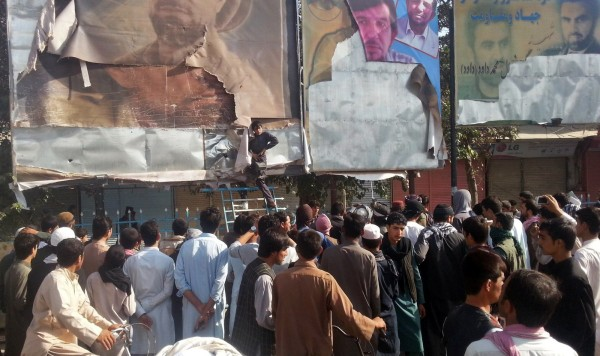 Image: A Taliban supporter removes leaders' pictures in Kunduz