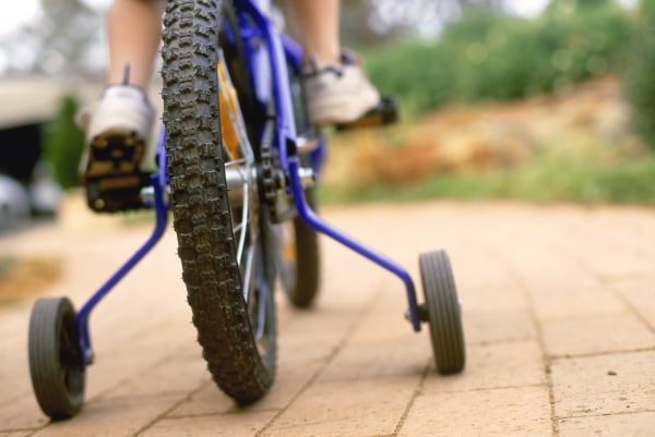 Photo: Child riding bicycle with training wheels.