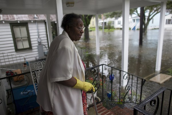 Image: McKnight watches the level of floodwaters in the front yard of her Orange Street home in Georgetown, South Carolina