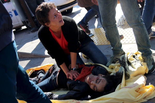 Image: A woman helps an injured woman after an explosion during a peace march in Ankara