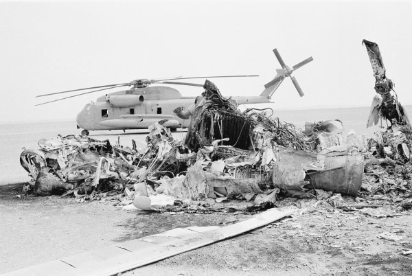 Image: Remains of a burned-out U.S. helicopter lies in front of abandoned chopper in the eastern desert region of Iran