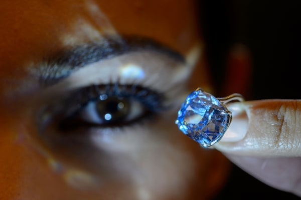 Image: A Sotheby's employee displays the rare Blue Moon Diamond