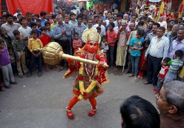 Image: A man dressed as Hindu monkey god Hanuman performs on a street during Hanuman Jayanti Festival in Allahabad