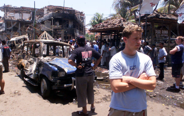 Image: Foreign tourists stand amid the chard remains of a bomb blast in Denpasar
