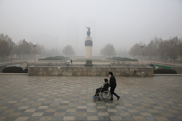 Image: A woman is pushed in a wheelchair in Baoding, China