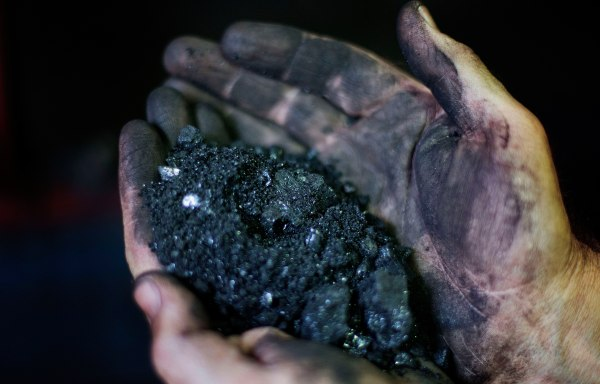 Image: Jackie Ratliff, a coal miner of 25 years, holds coal running through a processing plant