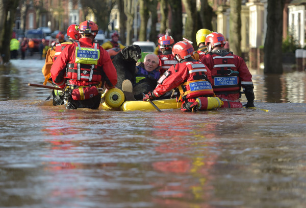 Image: A rescue team helps to evacuate people from their homes