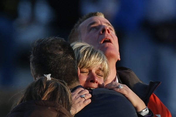 Image: The families of victims grieve near Sandy Hook Elementary School, where a gunman opened fire on school children and staff in Newtown, Connecticut