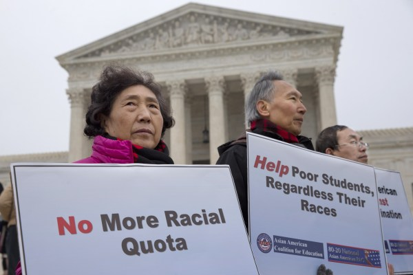 Guixue Zhou of North Potomac, Md., left, and others, protests against racial quotas outside the Supreme Court in Washington