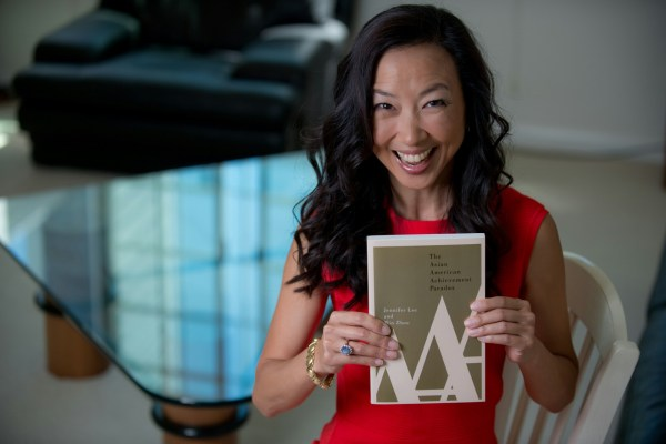 "UC Irvine professor Jennifer Lee with a copy of ""The Asian American Achievement Paradox,"" which she co-wrote with UCLA professor Min Zhou"