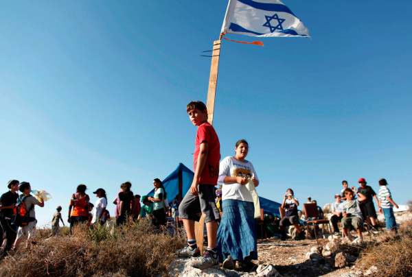 Image: Jewish settler youths gather on a hilltop near the West Bank settlement of Avnei Hefetz