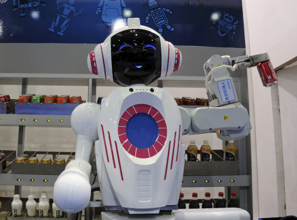 Image: A sales assistant robot picks up a can of Coca-Cola during a demonstration at the World Robot Conference in Beijing