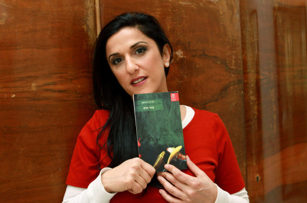 "Image: Israeli author Dorit Rabinyan poses with her Hebrew-language novel titled ""Gader Haya"""