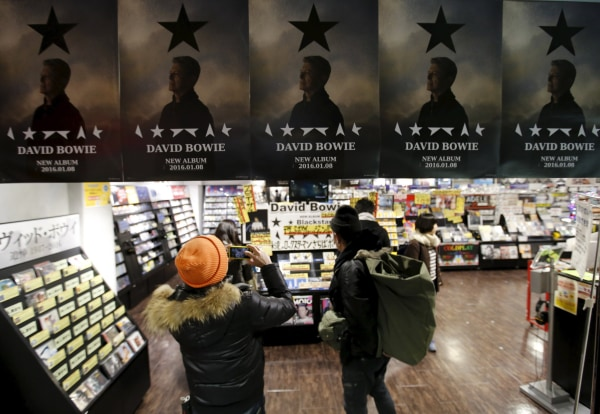 "Image: A Japanese fan takes a photo of posters depicting British rock star David Bowie's last album ""Blackstar"" displayed at a music retailer in Tokyo"