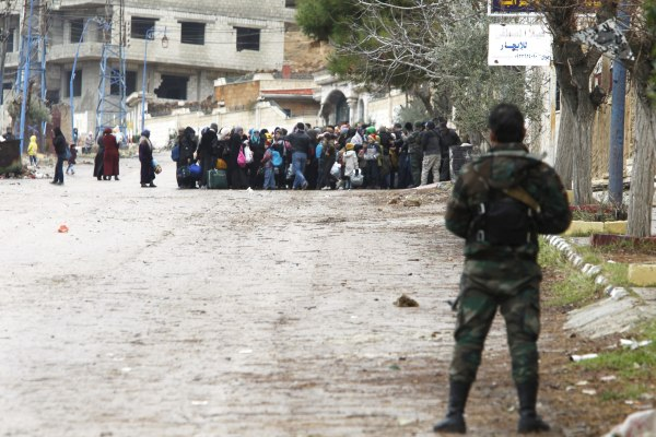 Image: Syrian Army soldiers monitor residents who said they have received permission from the Syrian government to leave the besieged town as they wait with their belongings after an aid convoy entered Madaya, Syria