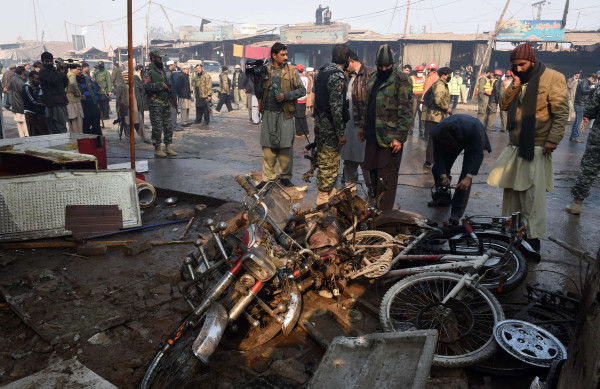 Image: Pakistani security officials examine the site of a suicide bomb attack on the outskirts of Peshawar