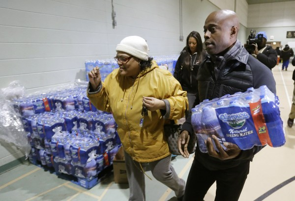 Image: R&B singer Kem helps Mwamini Wallace carry bottled water to her vehicle in Flint