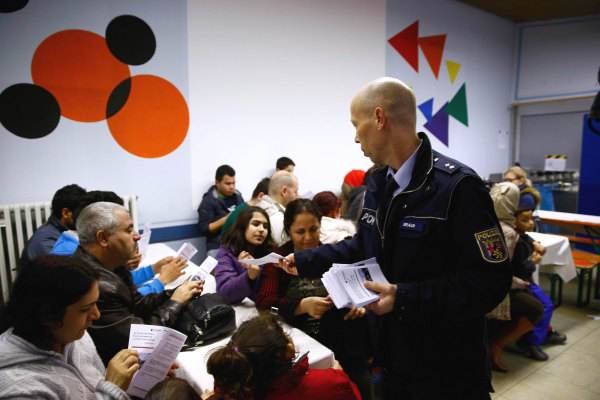 Image: Police officer hands out information leaflets on social etiquette ahead of the carnival season at refugee camp in Mainz