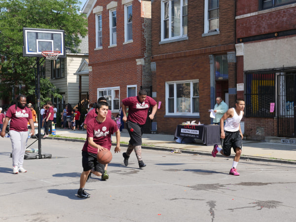 Children and adults playing basketball in the street in Pilsen