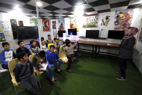 Image: A teacher gives a lesson to orphans boys at the Iraqi Safe House for Creativity in Baghdad