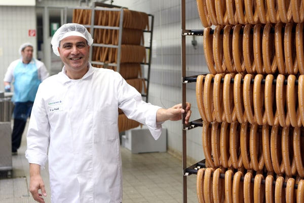 Image: An employee stands alongside sausages at the Volkswagen-owned butchery in Wolfsburg