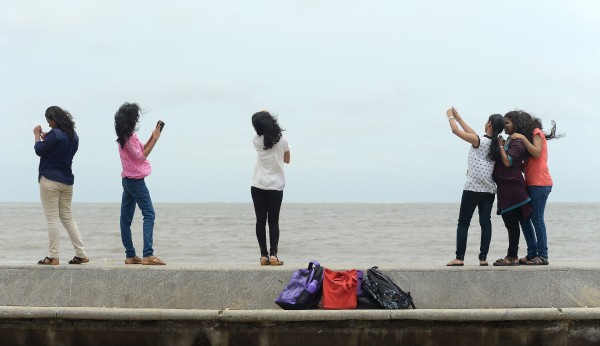 Image: Young Indian couples take 'selfies' on Marine Drive promenade in Mumbai.