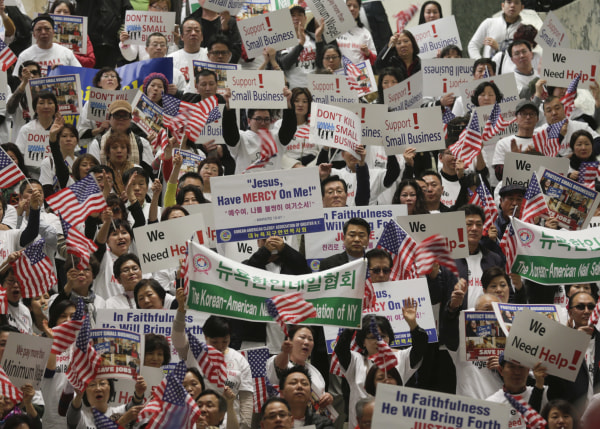 Image: New York nail salon owners and workers wave flags and signs during a small business advocacy rally in the Legislative Office Building on Monday, Feb. 29, 2016, in Albany, N.Y.