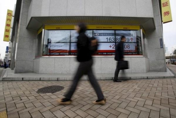 Pedestrians walk pass an electronic board outside a brokerage in Tokyo