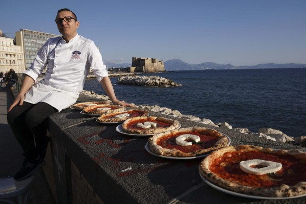 Image: Italian chef Gino Sorbillo shows his pizza with the words
